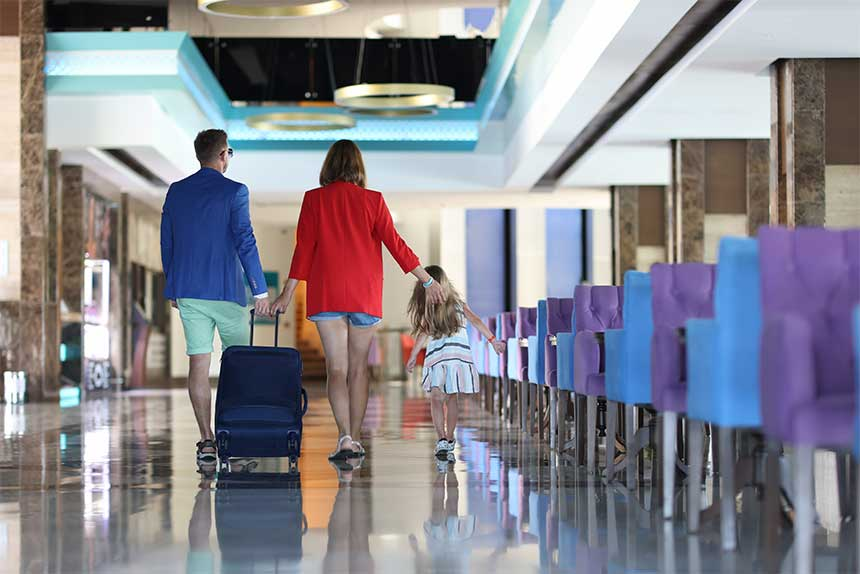 Jeune homme avec sa femme et leur fille avec une valise en voyage